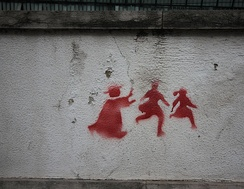 2011 graffiti in Portugal depicting a priest chasing two children.