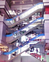 "Crisscross layout of escalators at Mahboonkrong Center, widely known as the MBK Center, in Bangkok. Such layouts are used to minimize structural space requirements by ""stacking"" escalators that go in one direction."