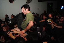 "A crowd of moshers, with a few people ""crowdsurfing"" on top of the mosh pit."