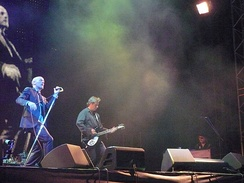 R.E.M. performing onstage, with Michael Stipe singing, Peter Buck playing guitar, and Scott McCaughey playing keyboards