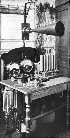 One of the crude pre-vacuum tube AM transmitters, a Telefunken arc transmitter from 1906.  The carrier wave is generated by 6 electric arcs in the vertical tubes, connected to a tuned circuit.  Modulation is done by the large carbon microphone (cone shape) in the antenna lead.
