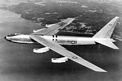 Side, black and white view of an early B-52, which features the bubble canopy. The aircraft is heading to sea, leaving behind the coastline on its right wing.