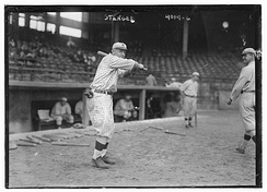 A man in an old-fashioned baseball uniform holds his bat above his shoulder, left-handed