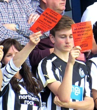 "Newcastle fans show ""Mike Ashley Out"" cards away to QPR, May 2015"