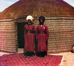Two Turkmen men standing on a Halı main carpet with Tekke göl, in front of a yurt. (1905-1915)