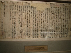 A tattered, ripped and crumpled piece of light coloured paper with writings penned in Chinese chearacters in dark ink, pinned on a wall for display in a museum.
