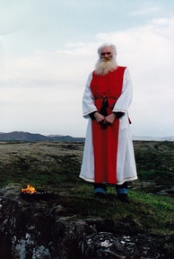 An elderly man wearing red and white robes standing in an open area