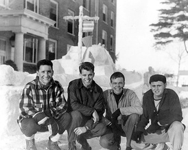 Kennedy (second from left) during his time at Bates College, in front of a snow replica of a Navy boat.