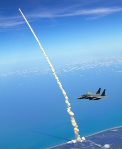 336th F-15E patrols over Florida as the Space Shuttle Atlantis launches in the background