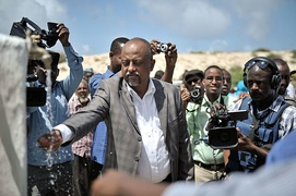 Official tastes the water of a new well in front of journalists in Mogadishu, Somalia, 2014.