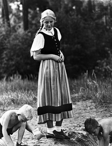 A young German girl in dirndl watching boys playing. (Propaganda photo from the Office of Racial Politics of the Nazi Party, 1933)