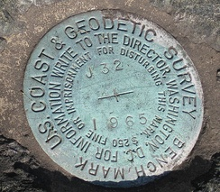Closeup of a United States Coast and Geodetic Survey marker embedded in a large rock in front of the Noroton Volunteer Fire Department in Darien, Connecticut.