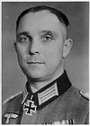 A black-and-white photograph of a man wearing a dark military uniform with a neck order in shape of an Iron Cross.