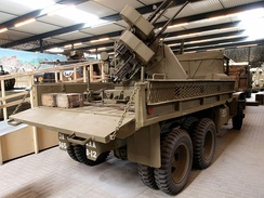 CCKW-353-B2 gun truck with M45 Quadmount on M20 trailer in bed, loading ramps attached to side
