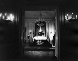 United States President John F. Kennedy lies in repose in the White House East Room.