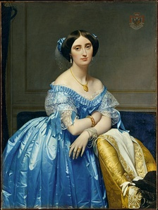 The Princesse de Broglie wears a blue silk evening gown with delicate lace and ribbon trim. Her hair is covered with a sheer frill trimmed with matching blue ribbon knots. She wears a necklace, tasseled earrings, and bracelets on each wrist.