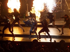"Gaga performing ""John Wayne"" while flamethrowers spit fire in the background"