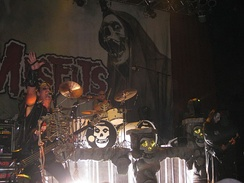 The rock band The Misfits performing onstage. The band's name in large lettering is printed on a fabric panel behind the performers along with a skull image. From left to right are the electric bassist, drummer, and electric guitarist.