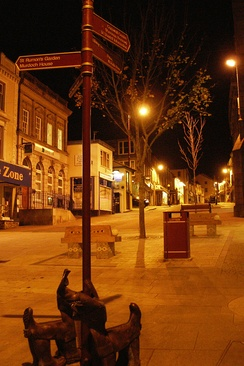 Redruth's Fore Street at night, showing one of the groups of bronze 'dogs'.