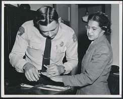 Rosa Parks being fingerprinted by Deputy Sheriff D.H. Lackey after being arrested for not giving up her seat on the bus to a white person