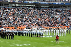 Service members of the U.S. Armed Forces at an American football event: (left to right) U.S. Marine Corps, U.S. Air Force, U.S. Navy and U.S. Army personnel