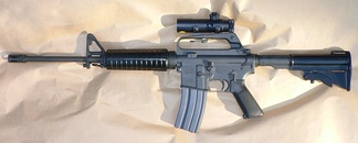 The Colt AR-15 carbine is a semi-automatic rifle that fires one round each time the trigger is pulled. The weapon features a pistol grip and a flash suppressor.