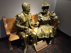 A life-size statue of Roy Acuff sits on a pew alongside a statue of Minnie Pearl in the lobby of Ryman Auditorium.