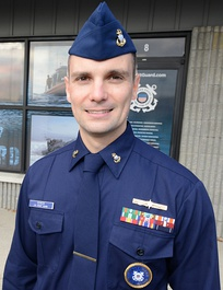A U.S. Coast Guard recruiter wearing the Winter Dress Blue uniform with garrison cap