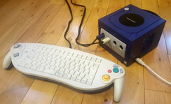 A GameCube with a broadband adapter installed and a connected ethernet cable. ASCII Corporation produced a keyboard controller to help players communicate in Phantasy Star Online.