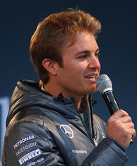 Man in his late twenties with a head full of hair and wearing a silver jacket. He is holding a microphone in his right hand.