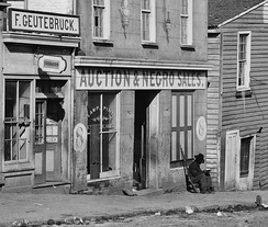 George N. Barnard's 1864 photograph of a slave trader's business on Whitehall Street, Atlanta, Georgia, shows a United States Colored Troop Infantryman [Corporal] just by the door.