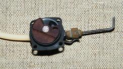 Газораспределительный механизм двухтактного двигателя с вращающимся дисковым золотником, установленным в задней части картера, под золотником видно частично открытое впускное окно.