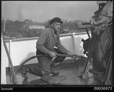 Boatswain of Felix von Luckners yacht Seeteufel, smoking a pipe and hosing the vessel's deck