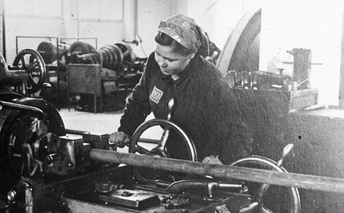 "Ostarbeiter on lathe at Monowitz, identified by ""Ost"" badge on her clothes"