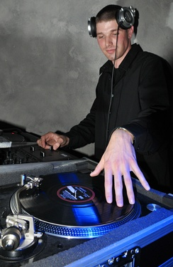 A disc jockey performing at the 2009 Air Force Ball. With one hand he is manipulating a vinyl record on a turnable; the other hand is controlling the mix with a DJ mixer.
