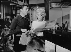 Monroe and Montand standing next to a piano in a studio-type setting and looking at sheet music.