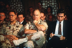 Gen. Colin Powell (left), Gen. Norman Schwarzkopf, Jr., and Paul Wolfowitz (right) listen as Secretary of Defense Dick Cheney addresses reporters regarding the 1991 Gulf War.