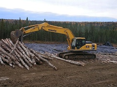 Tracked excavator placing corduroy on muskeg near Rocky Mountain House, Alberta