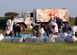 Workers from the UNHCR, and CARE International gather bundles of shelters and mosquito nets in Kenya