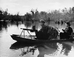 Viet Cong Guerrillas bear automatic weapons and use leafy camouflage as they patrol a portion of the Saigon River in small boats somewhere in South Vietnam.