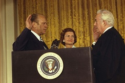 Gerald Ford is sworn in as the 38th President of the United States by Chief Justice Warren Burger in the White House East Room, while Betty Ford looks on.