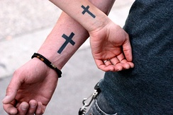 A Christian couple with matching cross symbol tattoos to associate with their faith