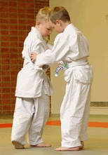 Two children training in judo techniques