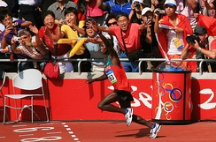 Samuel Wanjiru raises his hand in acknowledgment of the crowd as he runs to a gold medal in the 2008 Olympic marathon