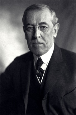 Half-length portrait of a man wearing a three-piece suit, a necktie, round-rimmed glasses and looking directly towards the photographer with an emotionless expression.