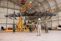 Yellow crane hoisting a wing of an aircraft, with several people standing below securing the wing. This takes place inside an aircraft hangar.