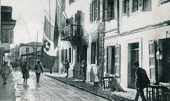 The flag of Italy shown hanging alongside an Albanian flag from the balcony of the Italian prefecture in Vlorë, Albania during World War I