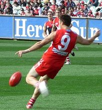 Nick Malceski executing a drop punt in 2006. In Australian rules football, squad numbers are usually not relevant to the player's position on the ground, although some clubs assign #1 to captains