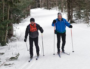 A blind cross-country skier with guide at a regional Ski for Light event.