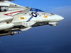 An upgraded F-14D(R) Tomcat with the ROVER transmit antenna circled with USS Theodore Roosevelt in the background